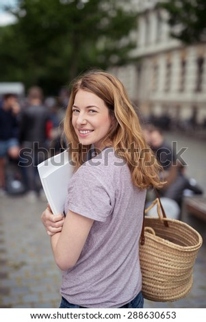 Pretty Teen Girl Student Carrying her Bag and Some Documents, Smiling at the Camera from her Back While Walking at the Street.