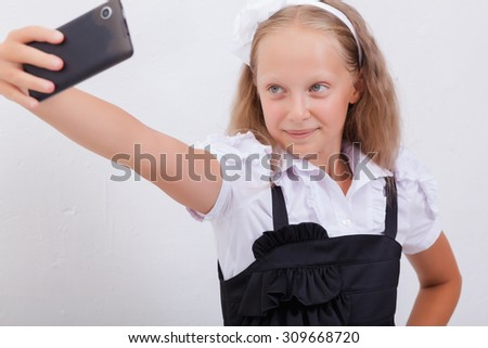 pretty teen girl taking selfies with her smart phone on white background