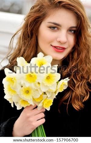 pretty teen girl with daffodils  - stock photo