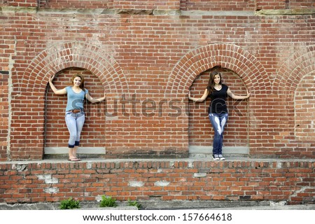 Pretty teen girls in the archways of an old brick warehouse. - stock photo
