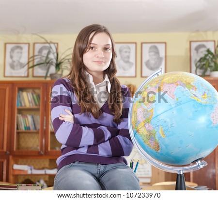 Pretty teen schoolgirl with globe in classroom - stock photo