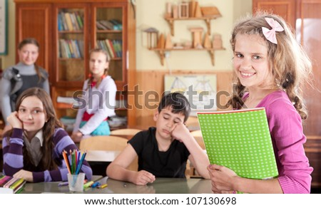 Pretty teen schoolgirl with notebook in front of class - stock photo