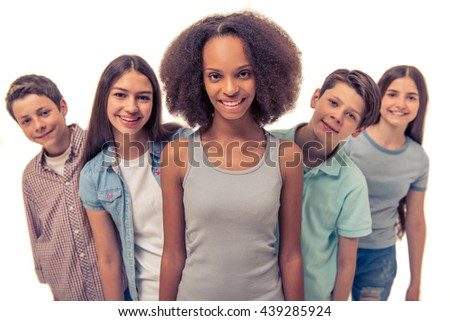 Pretty teenage Afro American girl is looking at camera and smiling, standing among other teenagers, isolated on white
