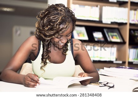 Pretty teenage black african college student girl smiling and reading a book in the library - stock photo
