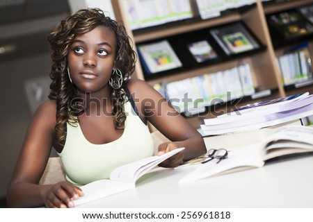 Pretty teenage black african college student girl studying and reading a book in college library - stock photo