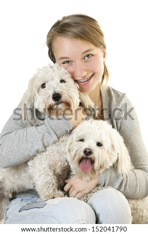 Pretty teenage girl holding two adorable coton de tulear dogs - stock photo
