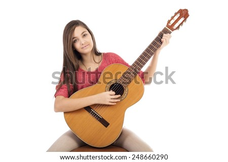 Pretty teenage girl playing an acoustic guitar  isolated over white background - stock photo