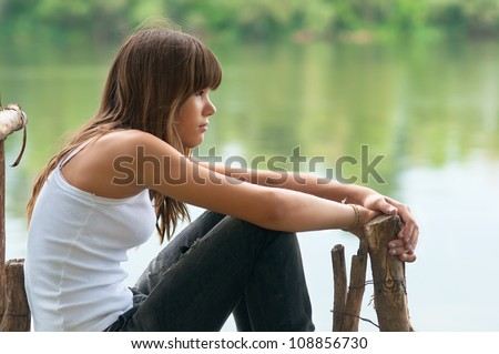 Pretty teenage girl sitting on the dock beside the river on beautiful summer day. - stock photo