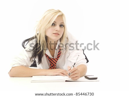 Pretty teenage school girl doing homework and cellphone