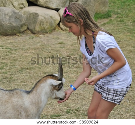 Pretty teenager feeding a goat - stock photo