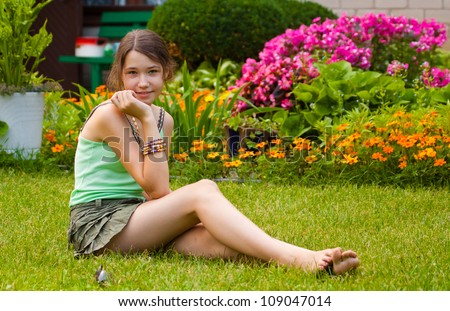 Pretty teenager girl sitting on the grass in the garden - stock photo