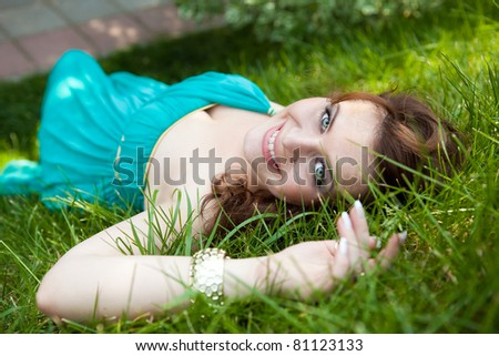 pretty teenager lying down on green grass in blue dress