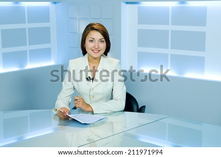 pretty television announcer at studio during live broadcasting - stock photo