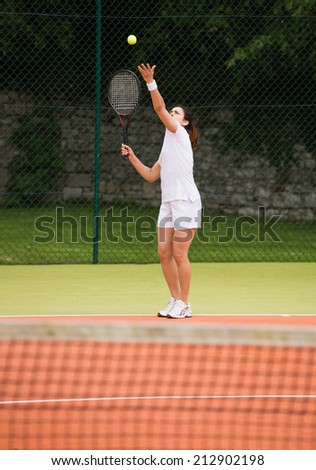 Pretty tennis player about to serve on a sunny day