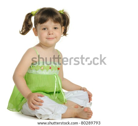 Pretty the little girl sits on the white. It is isolated on a white background