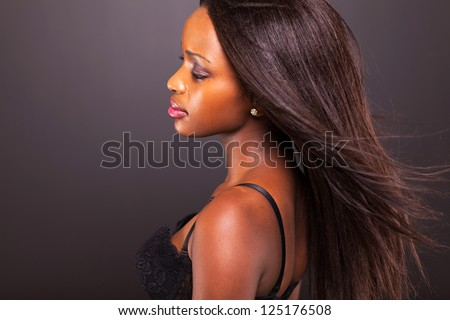 pretty thoughtful african american woman on black background - stock photo