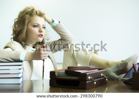 Pretty thoughtful sensual business woman sitting at table with many office appliances holding knife for cutting paper looking forward on white background copyspace, horizontal picture - stock photo