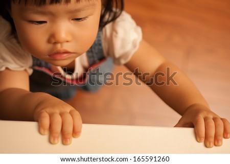 Pretty toddler asian girl grabbing edge of table - stock photo