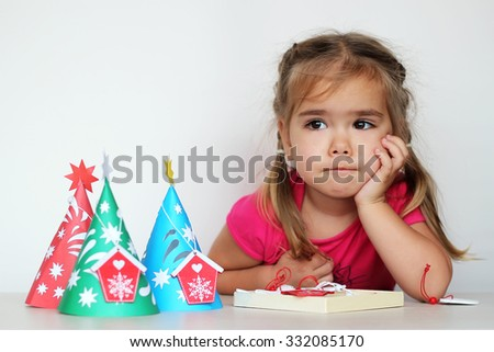 Pretty toddler girl dreaming near the handmade New Year trees on white background, indoor portrait