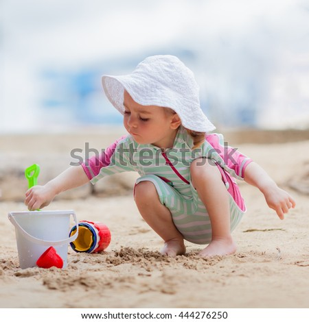 Pretty toddler girl in spf solar suit and hat playing with sand toys at the beach. Safety in summer sun. - stock photo