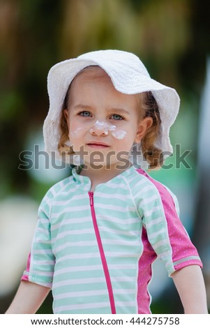 Pretty toddler girl in spf solar suit, hat and with sunscreen cream on her face playing at the beach. Safety in summer sun. - stock photo