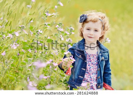 pretty toddler girl in spring near the flowers - stock photo