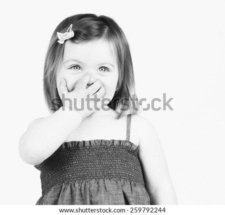 Pretty toddler girl with fingers over her mouth - stock photo