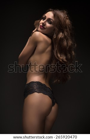 pretty topless girl back in black panties - stock photo