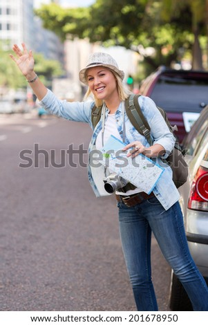 pretty tourist hailing a cab in the street  - stock photo