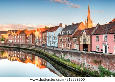 Pretty town houses overlooking the river Yare at Norwich in Norfolk with the cathedral spire in the background - stock photo