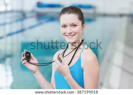 Pretty trainer blowing whistle and looking at stopwatch at the pool - stock photo