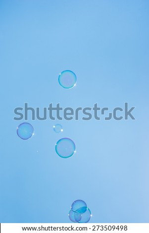 Pretty transparent iridescent bubbles floating against a sunny clear blue sky in a conceptual image. - stock photo