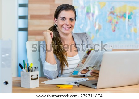 Pretty travel agent reading magazine in the office - stock photo