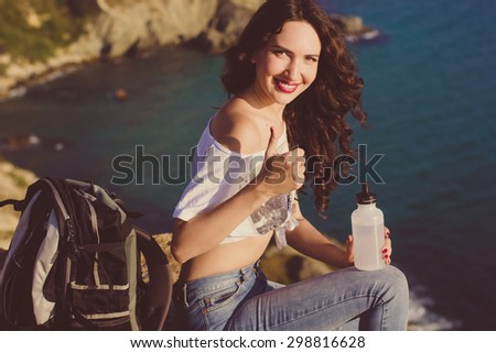 Pretty traveler girl backpacker is drinking water on rock peak over sea view with backpack, summer time - stock photo