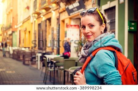 Pretty traveler girl on a street in european town - stock photo