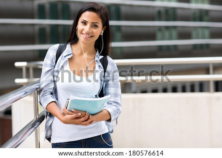 pretty university student holding books on modern campus - stock photo