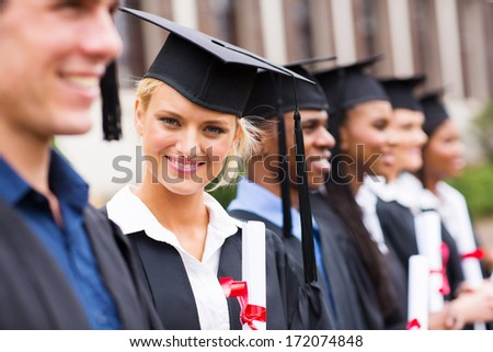 pretty university student in graduation attire looking at the camera - stock photo