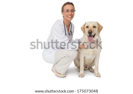 Pretty vet petting yellow labrador dog smiling at camera on white background - stock photo