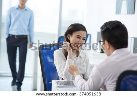 Pretty Vietnamese business lady flirting with her colleague in the office