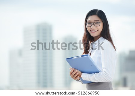 Pretty Vietnamese business lady with folder smiling and looking at camera