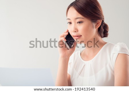 Pretty Vietnamese lady talking on the phone while reading document - stock photo