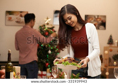 Pretty Vietnamese woman laying the table while her husband decorating Christmas tree