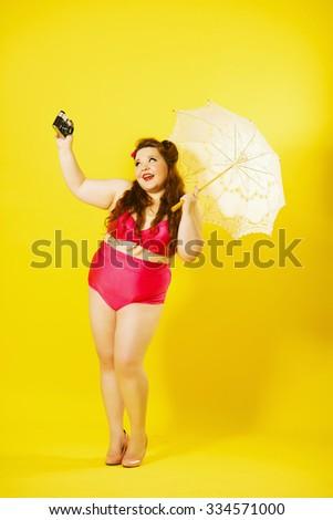 Pretty vintage plus size woman with lace white umbrella making selfie using retro camera.   - stock photo