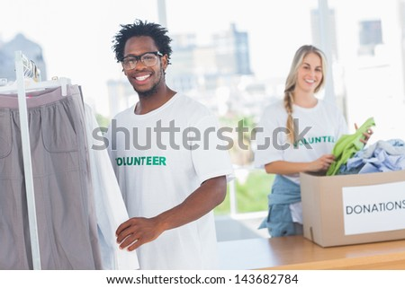 Pretty volunteers taking clothes out of a donation box in their office