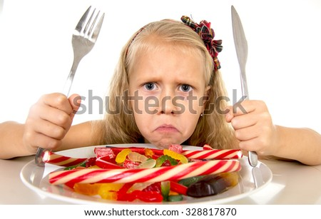 pretty vulnerable Caucasian female child eating dish full of candy holding fork and knife  in sweet sugar abuse dangerous diet and unhealthy nutrition concept isolated on white background - stock photo