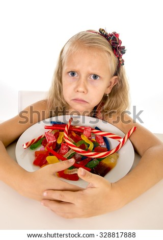 pretty vulnerable Caucasian female child eating dish full of candy holding the dish in sweet sugar abuse dangerous diet and unhealthy nutrition concept isolated on white background - stock photo