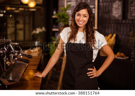 Pretty waitress posing next to coffee machine at coffee shop