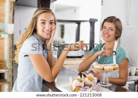 Pretty waitress serving cupcake to customer at the coffee shop - stock photo