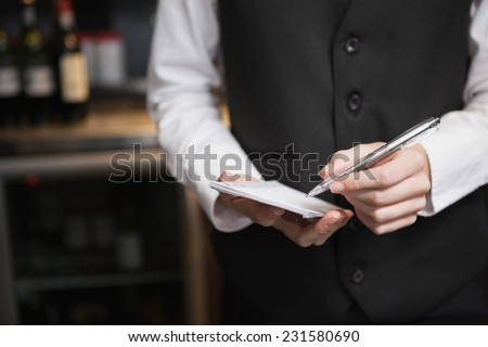 Pretty waitress taking an order in a bar - stock photo