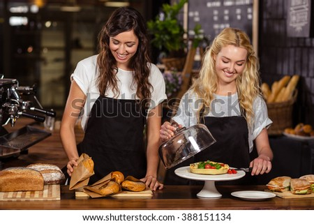 Pretty waitresses behind the counter at the coffee shop - stock photo